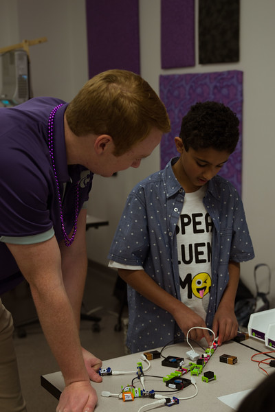 Future teacher and K-State student helps young visitor with the different electronics in the science room of Bluemont at Open House on Saturday. During K-State's Open House the education department filled Bluemont with fun activities in the science room, the animal room, the living wax museum, and other fun filled rooms. (Hannah Greer | Collegian Media)