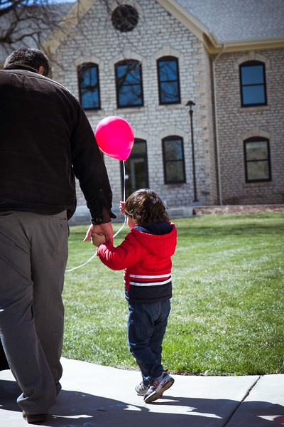 With balloon in one hand and father's hand in the other the young boy is ready to head home after a fun day at the Open House on Saturday, April 7. K-State had games, food, and even a bouncy castle for kids to enjoy. (Hannah Greer | Collegian Media)