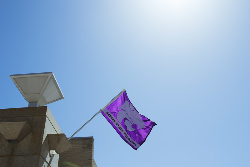 Kansas State Wildcats flag waves proud and high at Open House on Saturday, April 7 as families fill the campus for a day full of purple. K-State's Open House was filled with fun activities, food, and plenty of opportunities to explore the vast options K-State has to offer. (Hannah Greer | Collegian Media)