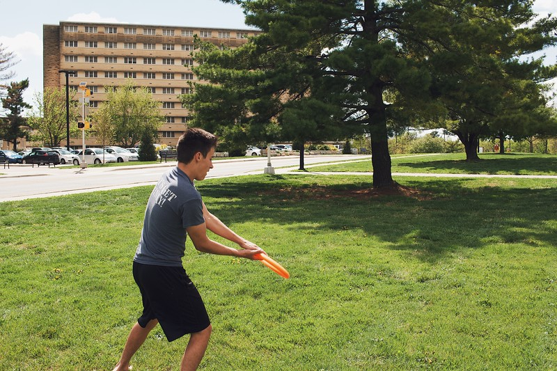 Carson Hughes, freshman in chemical engineering, grasps an incoming frisbee. Frisbee is just one of the many outdoors activities you can enjoy during the warm weather. (Katelin Woods | Collegian Media Group)
