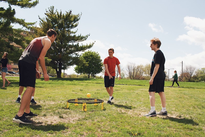A group of Kansas State University students play Spike Ball in the grass across the street from Haymaker hall. (Katelin Woods | Collegian Media Group)