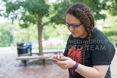Katie Bradshaw, junior in biology, checks her phone for nearby Pokemon's outside of Kedzie Hall on July 12, 2016. Bradshaw said she used to play the card and Gameboy games as a child. (Evert Nelson | The Collegian)