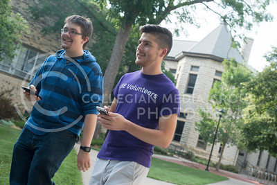 Chris Allmon, (right) University of Kansas student, walks with Tyler Robinson, graduate student in computer science, in front of Kedzie Hall on July 12, 2016 while playing the Pokemon GO app on their phones. (Evert Nelson | The Collegian)