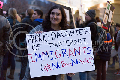 Jumanna Khamis, senior in marketing, holds a sign on campus during the Manhattan Kansas Solidarity Rally that was in held in Bosco Plaza on February 1, 2017. The rally was held in protest of President Trump's recent executive order regarding immigration. (Anna Spexarth | The Collegian)