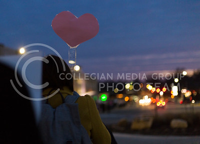 A rally-goer holds a heart sign on campus after the Manhattan Kansas Solidarity Rally that was in held in Bosco Plaza on February 1, 2017. The rally was held in protest of President Trump's recent executive order regarding immigration. (Anna Spexarth | The Collegian)
