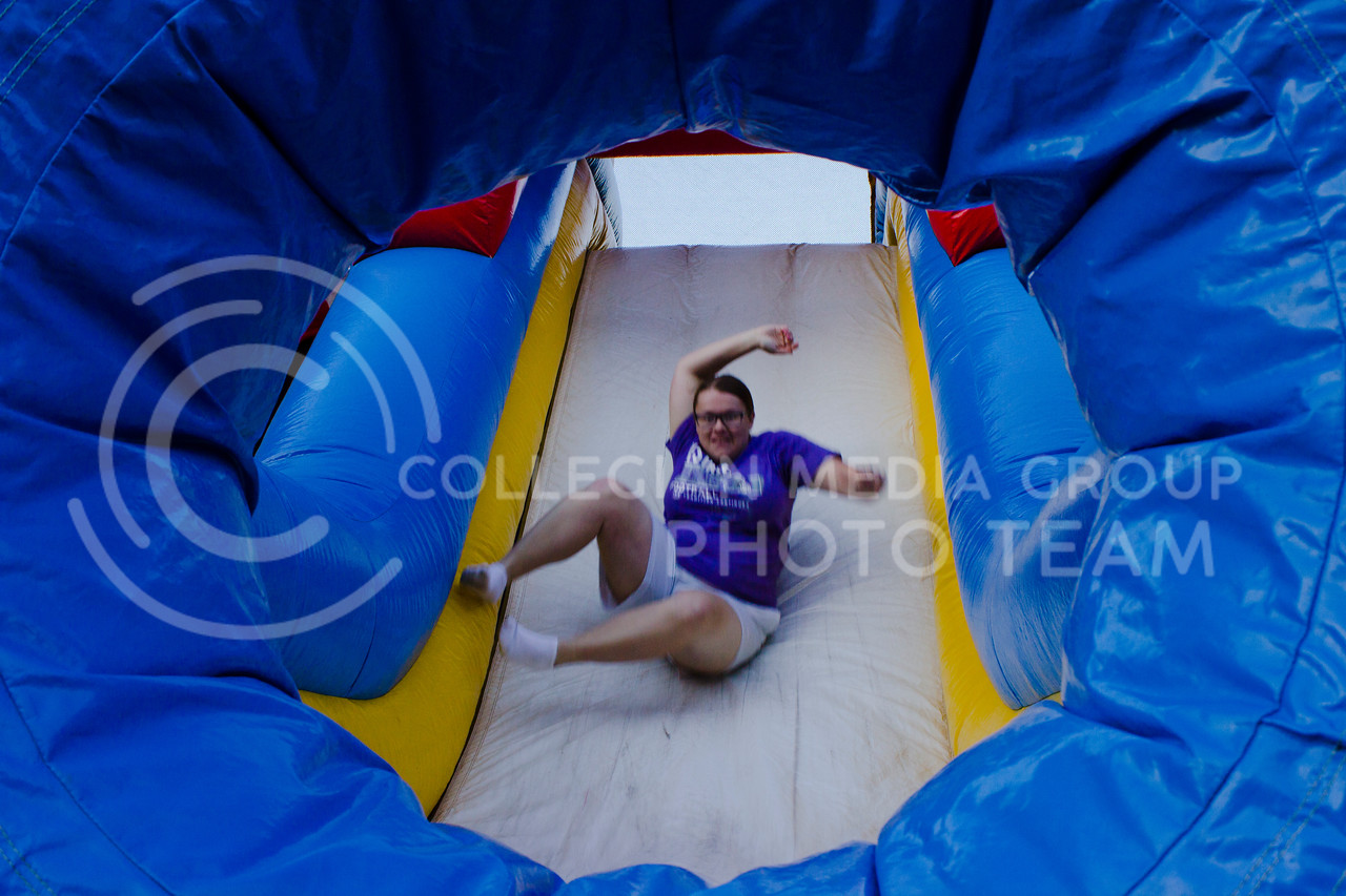 Harley Schuster, freshman in architecture, races to the bottom of an inflatable obstacle course at the Goodnow and Wefald block party. (Regan Tokos | The Collegian)