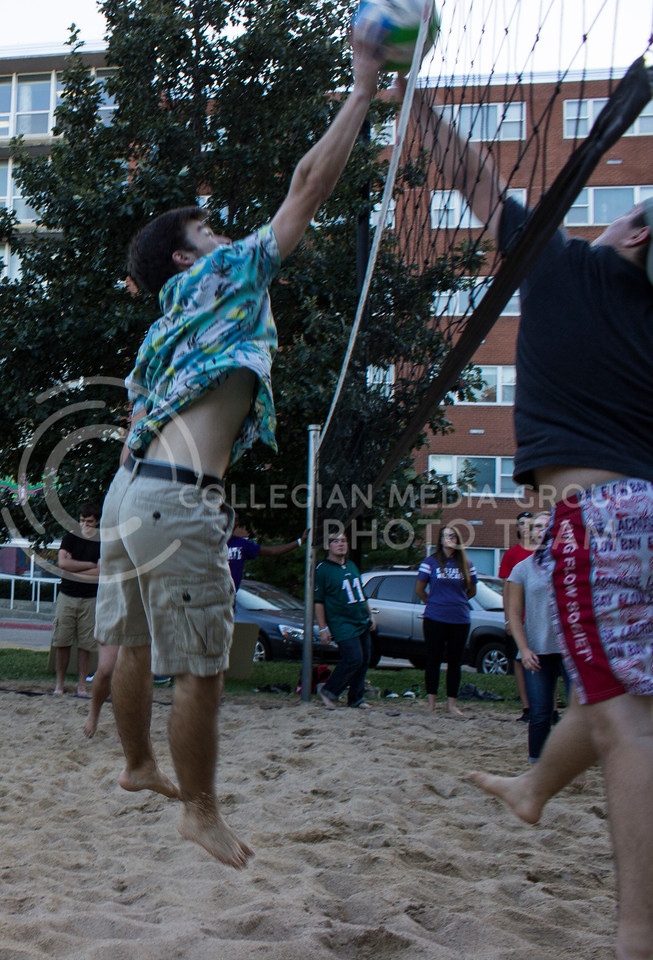 August Balman, freshman in vocal performance, blocks a hit from the Wefald team at an outdoor volleyball game between the Wefald and Goodnow residents halls at their block party. (Regan Tokos   The Collegian)