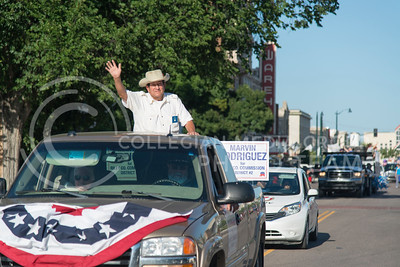 Marvin Rodriguez waves to patrons on Poyntz Avenue on July 21, 2016 during the Riley County Fair parade. Rodriguez is running for Riley County Commition District #2. (Evert Nelson | The Collegian)