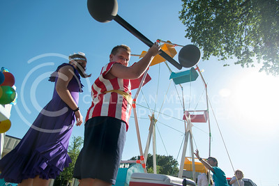 Cade Westfahl lifts a homemade dumbell made from pipe and balloons while on a parde float on July 21, 2016. The parade down Poyntz Avenue was for the Riley County Fair which kicked off Thursday and runs through July 25. (Evert Nelson | The Collegian)