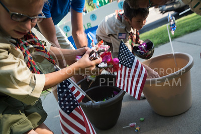 Boy Scouts grab handfuls of candy out of flower plants handeled by a Blueville Nursey employee during the end of the Riley County Parade on Poyntz Avenue on July 21, 2016. (Evert Nelson | The Collegian)