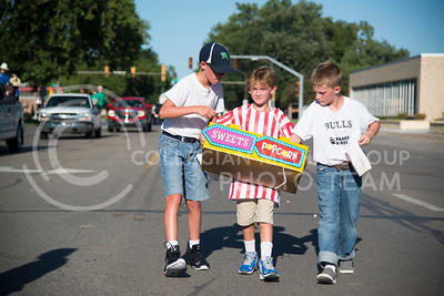 Lucas Holegrams (left) and Logan Crist-Funk (right) dig into Will Richards (middle) sweets and popcorn carrier at the end of the Riley County Parade route on Poyntz Avenue on July 21, 2016. (Evert Nelson | The Collegian)