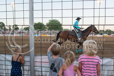 Kids press against the fence at Wells Arena in CiCo Park as a trick horseback rider rides in front of them on July 21, 2016. The act was part of the Kaw Valley Rodeo which goes along with the Riley County Fair July 21 through July 25.  (Evert Nelson | The Collegian)