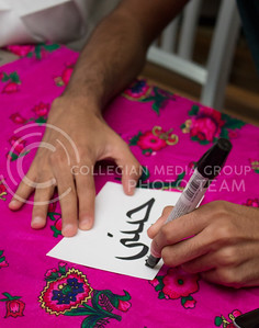 Abdulrhman Altamimi, junior in finance, writes names in Arabic during the National Day of Saudi Arabia celebration in the K-State Student Union courtyard on Oct. 6, 2016. (Miranda Snyder | The Collegian)