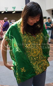 Yingjie Zhang, K-State alum, tries on traditional Saudi clothing during the National Day of Saudi Arabia celebration in the K-State Student Union courtyard on Oct. 6, 2016. (Miranda Snyder | The Collegian)