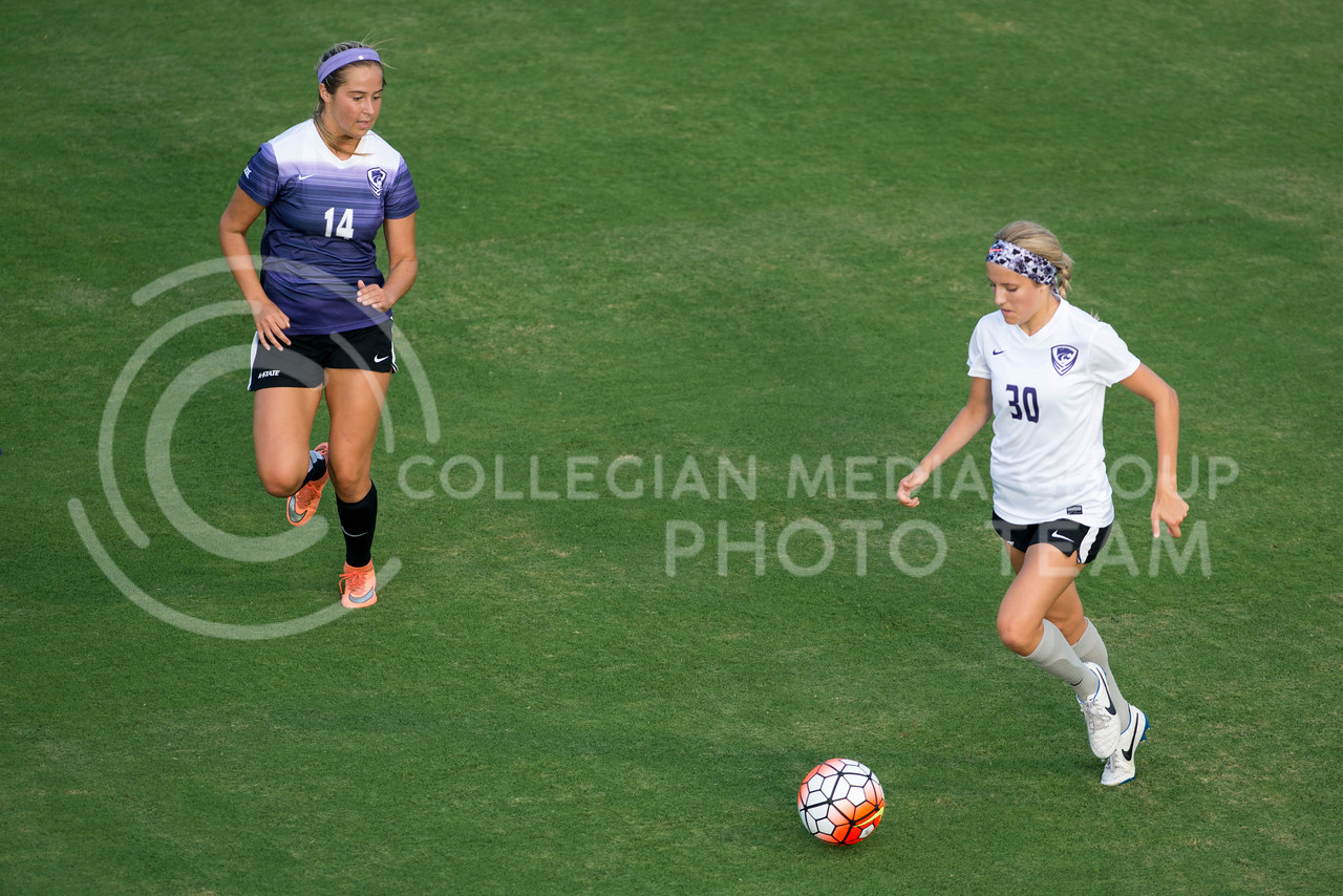 Bridget Howard, freshman, dribbles away from Ashley Zane, freshman, during the Wildcats first scrimmage at the K-State Soccer Complex on August 6, 2016. White defeated Purple 2-0. (Evert Nelson | The Collegian)