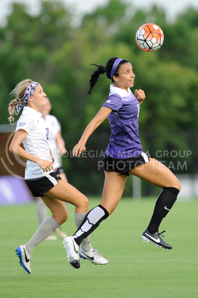Hali Sutter, sophomore, heads the ball away from Bridget Howard, freshman, during the first scrimmage of the Wildcat team on August 6, 2016 at the K-State Soccer Complex. White defeated purple 2-0. (Evert Nelson | The Collegian)