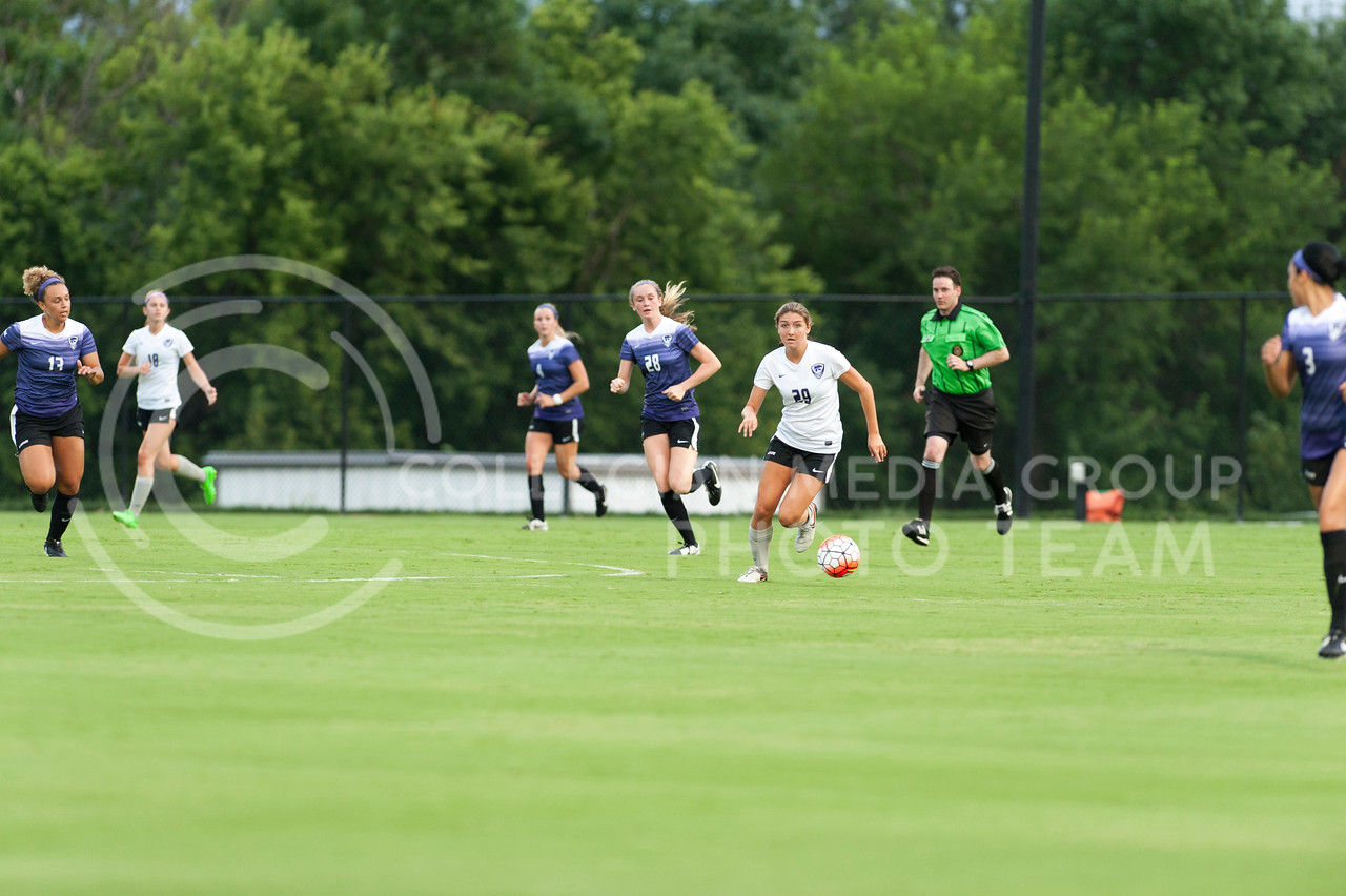 Olivia Covert, freshman, dribbles away from Purple defenders during the Wildcats scrimmage on August 6, 2016 at the K-State Soccer Complex. White beat Purple 2-0. (Evert Nelson | The Collegian)