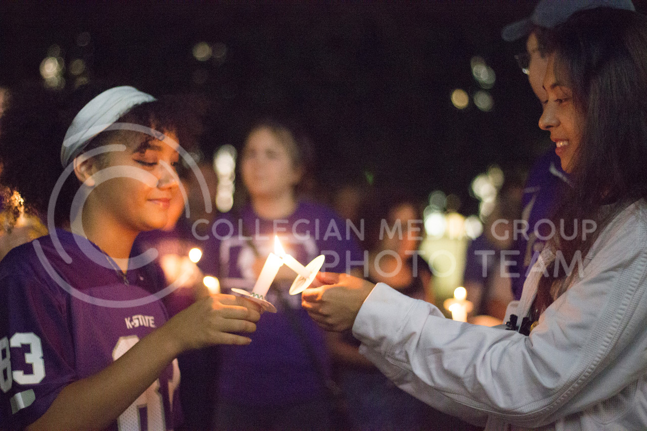 Freshmen Danielle Koger and Linda Toledo join to light their candles at the Solidarity rally at Bosco Plaza on Sept 14th, 2017. (Kelly Pham | The Collegian)