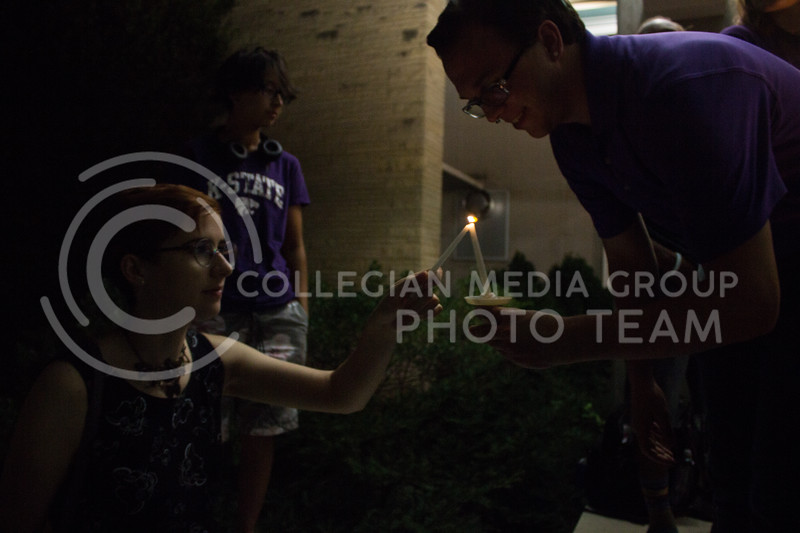 Seth Dills, senior in elementary education, and Cynthia Ferguson, junior in computer science, light each others candles at a solidarity rally held in Bosco Plaza on Sept. 14. The rally was held in response to white nationalist posters were seen on campus. (Regan Tokos | Collegian Media Group)
