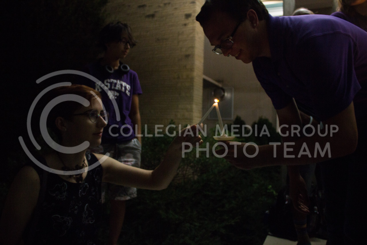 Seth Dills, senior in elementary education, and Cynthia Ferguson, junior in computer science, light each others candles at a solidarity rally held in Bosco Plaza on Sept. 14. The rally was held in response to white nationalist posters were seen on campus. (Regan Tokos   Collegian Media Group)
