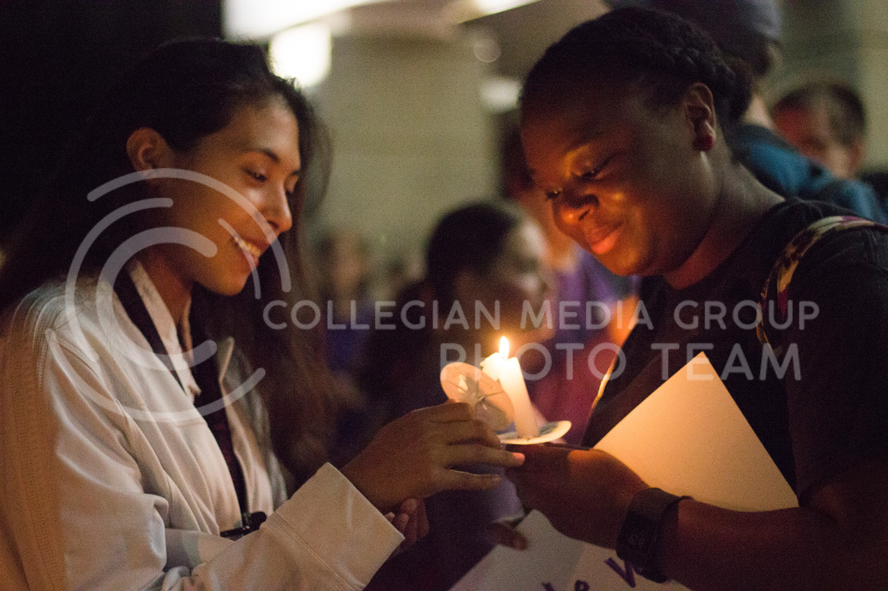 Freshman Linda Toledo passes on her flame to Sophomore DeAngelena Terrell at the Solidarity rally at Bosco Plaza on Sept 14th, 2017. (Kelly Pham   The Collegian)