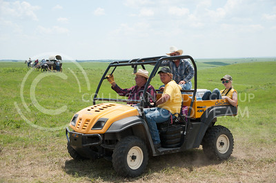 A modern all terrain vehicle drives in the foreground of the site for Symphony In The Flint Hills while a horse-drawn wagon moves into the distance on June 11, 2016. (Photo by Evert Nelson | The Collegian)