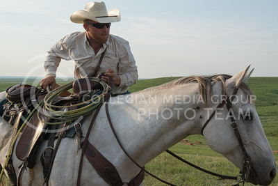 Jared Witman, Kansas resident, mounts his horse before taking off around the site for a cattle drive at sunset on June 11, 2016 at the Symphony In The Flint Hills. Besides the drive, the cowboys hung around the site talking with people and explaining what they do on a daily basis.  (Photo by Evert Nelson | The Collegian)