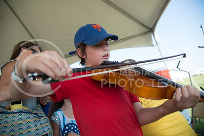 Nathan Friedman, eight year old Kansas resident, plays for the first time a violin in the Instrument Petting Zoo on June 11, 2016. Flint Hills Music donated the tent and instruments including strings, brass and a variety of drums. (Photo by Evert Nelson | The Collegian)