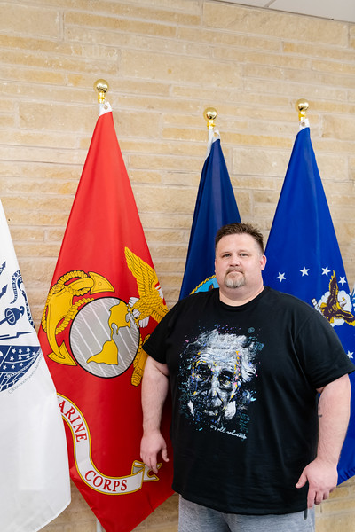 Donald Lawrence, a senior studying political science and history, stands in front of the Marine Corps flag where he previously served for 12 years as a Non-Commissioned Officer. (Olivia Bergmeier | Collegian Media Group)