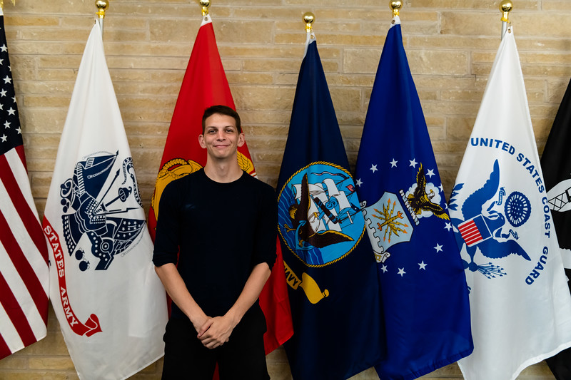 Standing in front of the flags at the Office of Veteran Affairs at the K-State Student Union Justin Colby, a sophomore studying arts and sciences/open option, poses for a picture. (Olivia Bergmeier | Collegian Media Group)