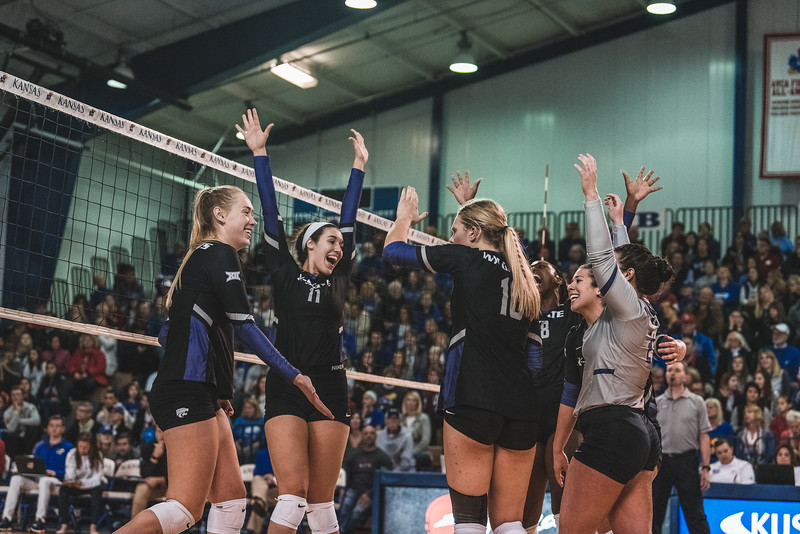 The Wildcats celebrate their second win of the night after completing the fourth set. K-State went on to defeat KU 3-2 on November 14, 2018 in Lawrence, KS. (Alex Todd | Collegian Media Group)