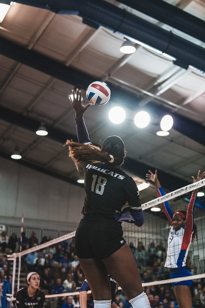 Jumping up for a spike, Gloria Mutiri scores a point for K-State during the volleyball game in Lawrence, KS on November 14, 2018. K-State beat KU 3-2. (Alex Todd | Collegian Media Group)