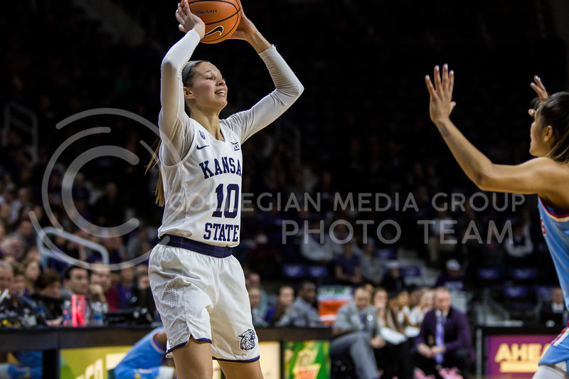 Junior guard, Kayla Goth, scans the court for an open teammate as she protects the ball against KU in Bramlage Coliseum on Feb. 24, 2018. The Wildcats defeated the Jayhawks 91-67. (Logan Wassall | Collegian Media Group)