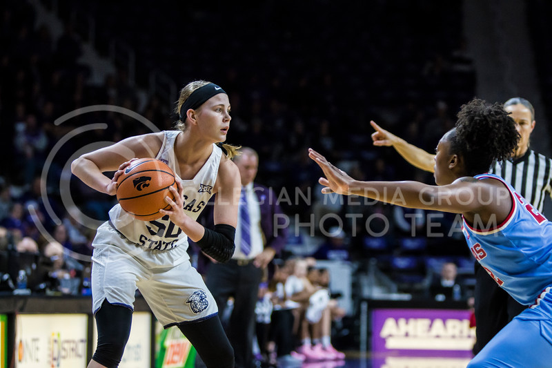 Senior guard, Shaelyn Martin, scans the court for an open teammate as she protects the ball against KU in Bramlage Coliseum on Feb. 24, 2018. The Wildcats defeated the Jayhawks 91-67. (Logan Wassall | Collegian Media Group)