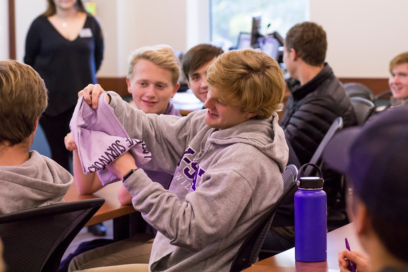 A participant looks at a t-shirt prize at a Wildcats Make a Pact session on Oct. 15 in the Business Building. Wildcats Make a Pact is a bystander intervention training that provides participants with the skills to help them intervene safely when they see behavior that puts others at risk for violence, victimization, or perpetration. (Andrea Klepper | Collegian Media Group)