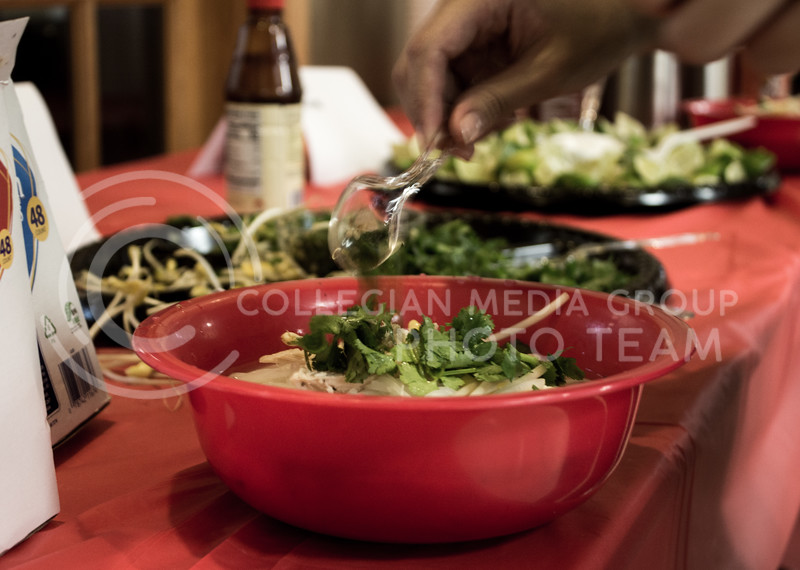 A student adds garnish to Pho, a vietnamese noodle soup, at the Wildcats Pho-Ever dinner on Oct. 29, 2017. The event was put on by Wildcats Forever and the Asian American Student Union. (Regan Tokos | Collegian Media Group)