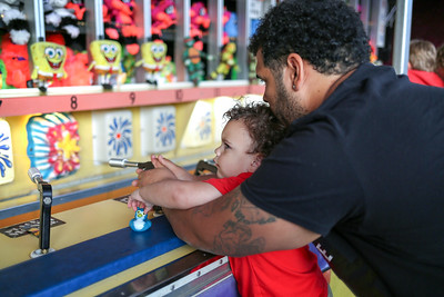 Jayden Mendez and his dad Jacob try their hand at the water gun game.  Photo by John Fitts