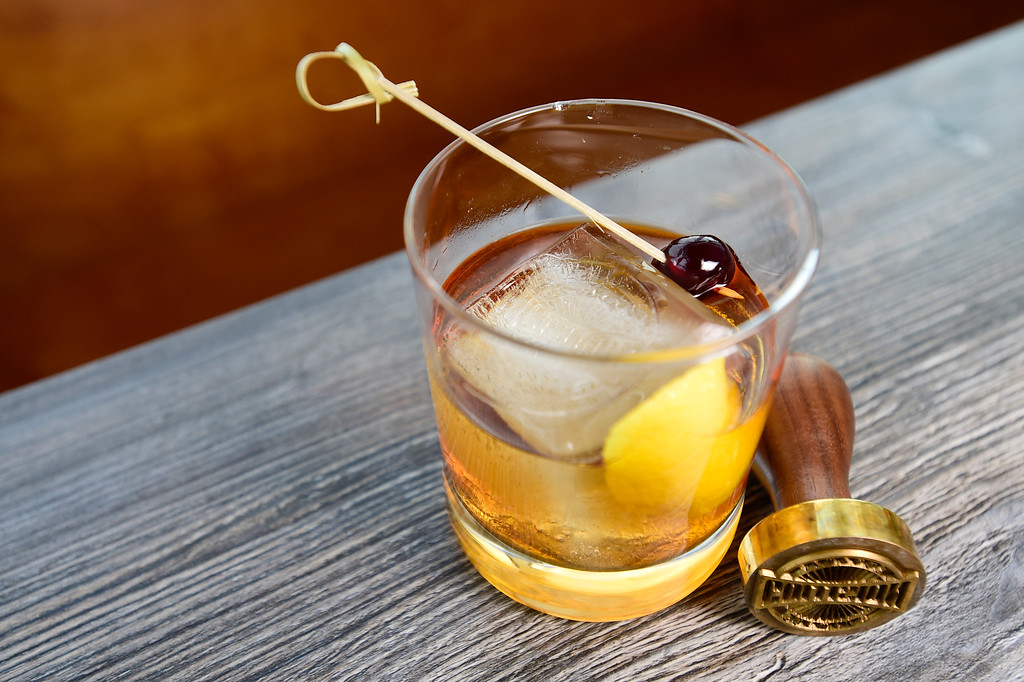 . LONGMONT, CO - JANUARY 30:EB Old Fashioned featuring Michter\'s Small Batch bourbon, aromatic old fashioned bitters, flamed lemon peel, house smoked Amarena cherries with a logo stamped ice cube at Collision Brewing Company and restaurant in Longmont on Jan. 30, 2019. (Photo by Matthew Jonas/Staff Photographer)