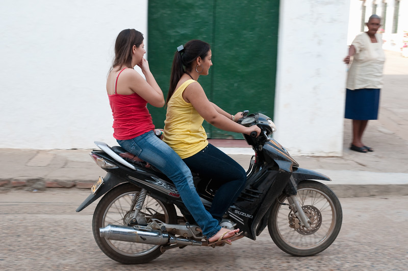 Young women on motorbike watched by elderly woman, Mompox (Mompós), Colombia.