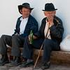 Elderly men sitting on a ledge, Villa de Leyva, Colombia.