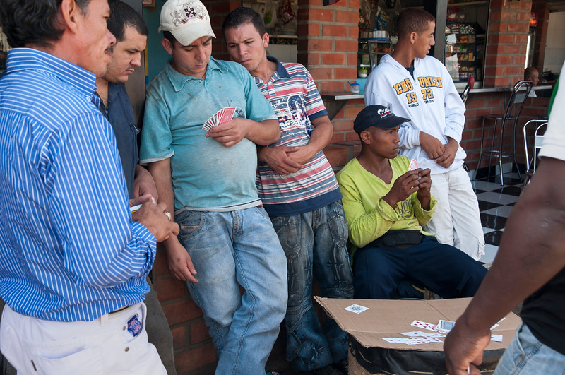Men play cards outside of indoor market, Medellin, Colombia