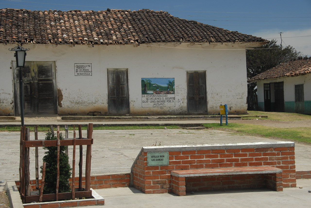 """The town of Santa Cecilia.  The colored sign on the building reads: """"Responsibility increases the repect one has for oneself.""""  The smaller sign on the building says: """"Do you love your town? Do not say it.  Do not write it.  Show it."""""""