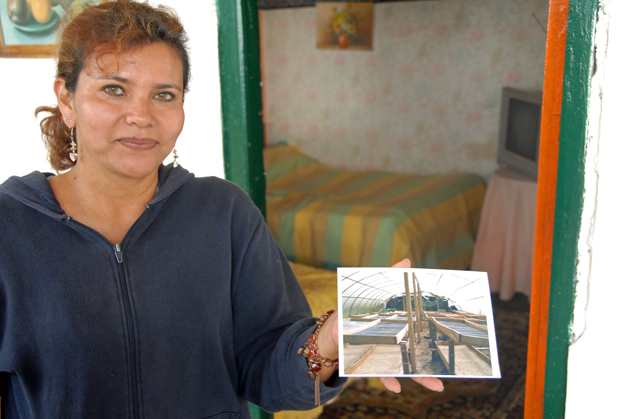Cecilia Diago, one of Maria Santos' daughters and who has been instrumental helping her mother in these late years, holds a photo in 2007 of the structure her mother wants to set up for drying coffee.