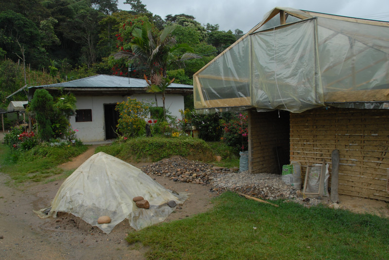 Isaias' home in the background.  In the foreground is a structure he built for drying his coffees, based on the parabola.