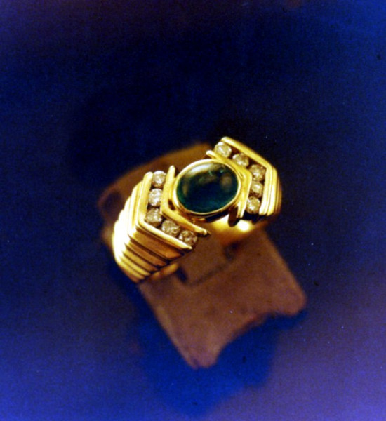 Cabochon cut emerald bezel set into a cast ring. This also illustrates some chnnel setting.