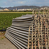 Irrigation Pipes Stacked Next to Field