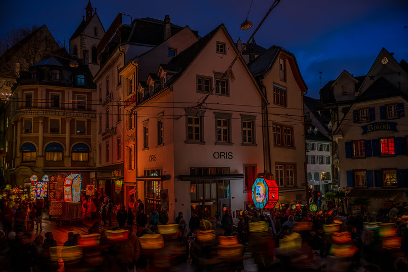 Merry Marching Lights. Morgestraich parade during the Basler Fastnacht. The city lights goes totally dark and thousands of people parade disguised with traditional masks and big lamps with political mockery. Lights marching in the blue hour of the morning, filling houses and windows with their merry atmosphere.