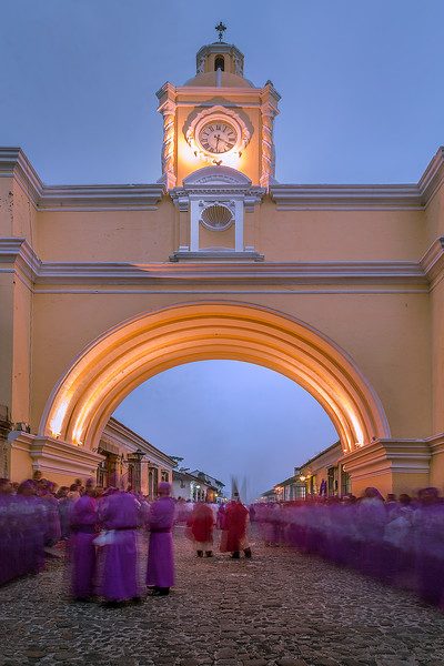Lent in Antigua. Slow walking penitentes through the Santa Catalina Arch in Antigua Guatemala, procession of San Bartolmé Becerra. UNESCO World Heritage.