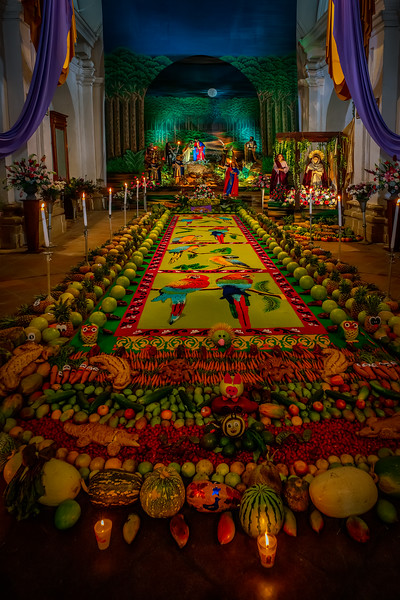 Velacion. Candlelight altar with sawdust carpets, fruits and vegtables offered to Jesus Christ with the cross, as part of syncretism of mayan and colonial catholic faith, preceding the holy week. San Cristobal El Bajo, Antigua Guatemala. UNESCO World Heritage.