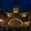 Shadows in Incense. Lights and shadows blend at the blue hour evening of the day, when hundreds of penitents incense the path of the Virgin Mary in the Solitude Saturday celebration of the Holy Week. View through the Santa Catalina arc in Antigua Guatemala, UNESCO world heritage.